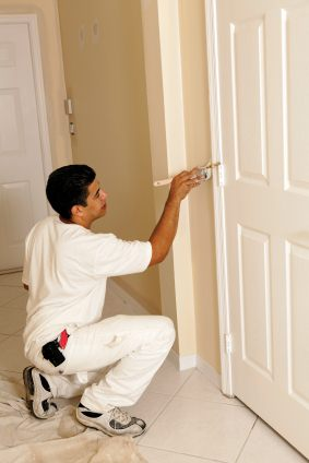 Painter painting interior of house. Painting the trim around a door white.